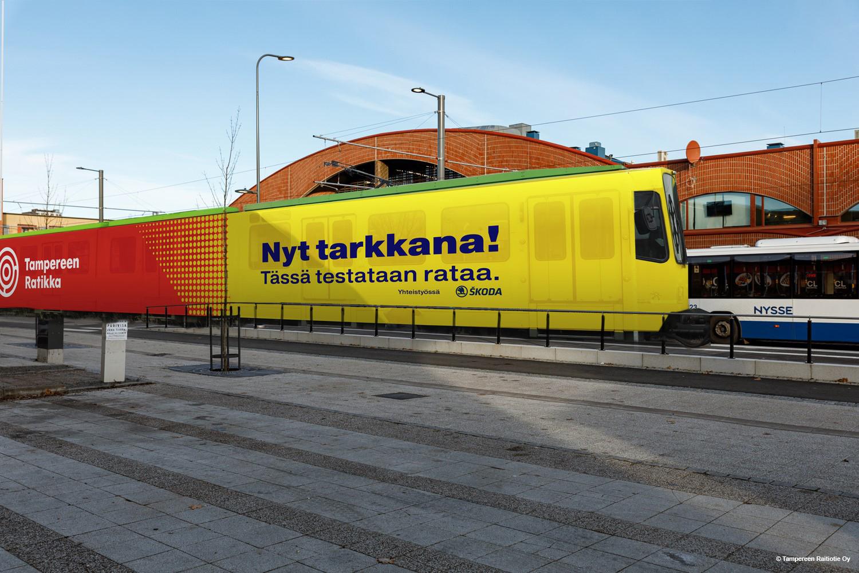 Tampereen Ratikan testivaunun havainnekuva. Testivaunu teipataan näyttävästi. Värityksessä näkyvät radan kunnossapitokaluston keltainen väri sekä Tampereen Ratikan vaunujen punainen väri.